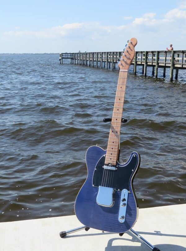 Blue Flame maple-topped tele on a stand by the water